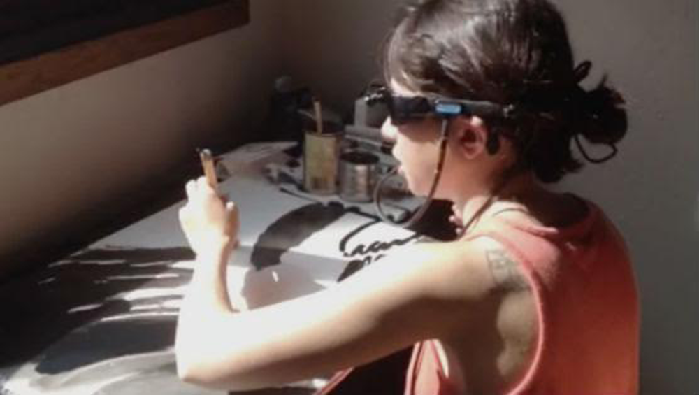 Emilie Gossiaux sits at a table and paints with black paint while wearing the Brainport Visions Device.