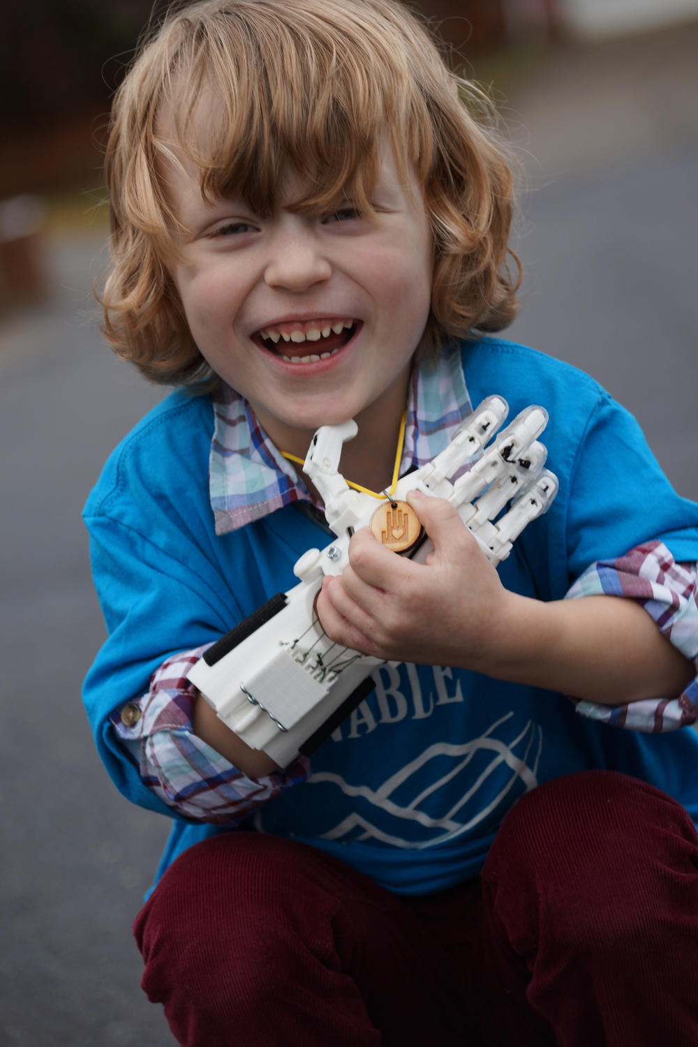 A laughing young boy squats, holding his right, 3D printed hand to his chest and holding an e-Nable necklace with his left hand.