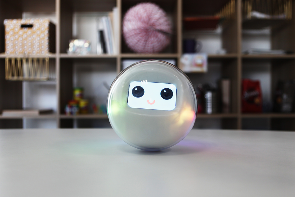 The smart toy Leka, a robotic sphere, rests on a table smiling through its digital interface.