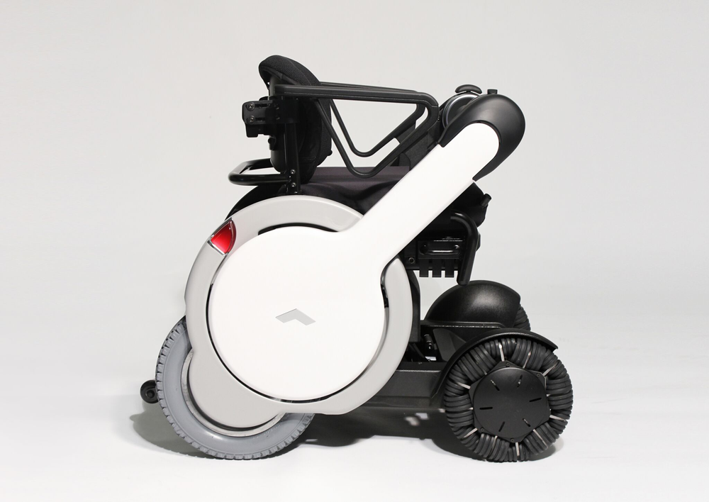 The WHILL is a modern black, white, and gray wheelchair with four wheels.