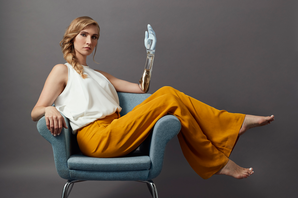 A woman seating sideways on designer chair wearing fashionable clothes and transparent and gold Alternative Limb