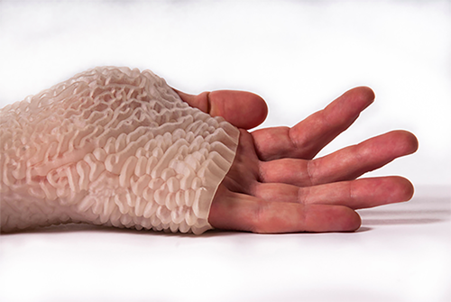 A close up of a human hand covered in the Carpal Skin prototype that is white with various ridges on the outside.
